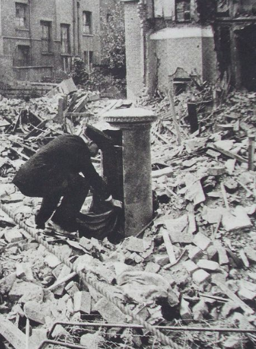 Postman collecting letters from a postbox surrounded by debris from world war 2